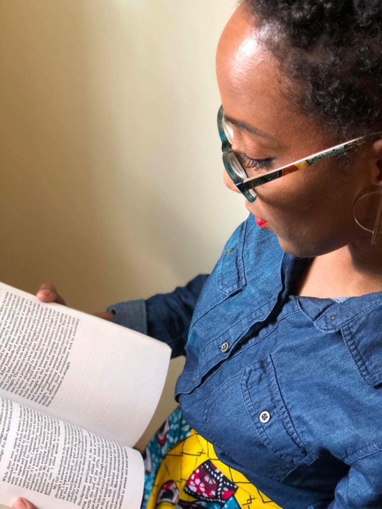 Black woman reading book African print skirt